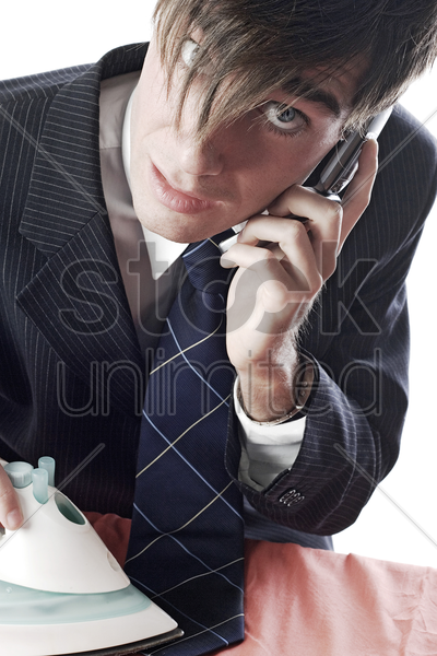 businessman talking on the cell phone while ironing his tie stock photo