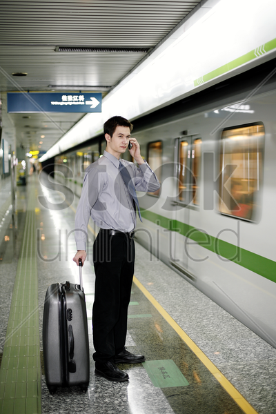 businessman talking on the hand phone while waiting for the train stock photo