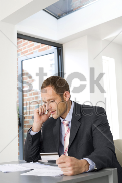 businessman talking on the mobile phone and holding credit card stock photo