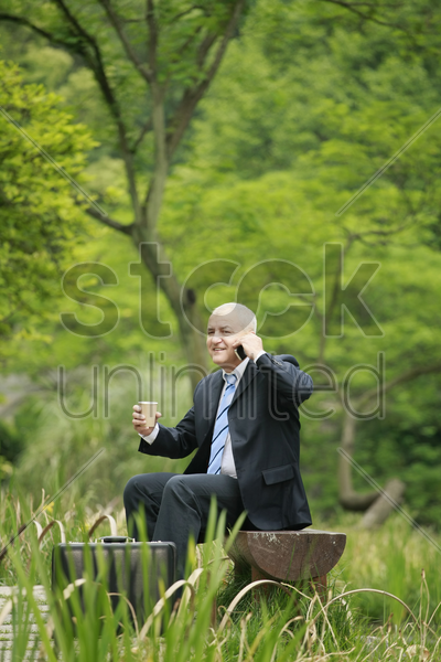 businessman talking on the phone and holding a cup of coffee stock photo