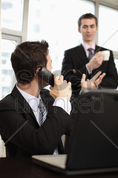 businessman talking on the phone and looking back at his colleague in the background stock photo