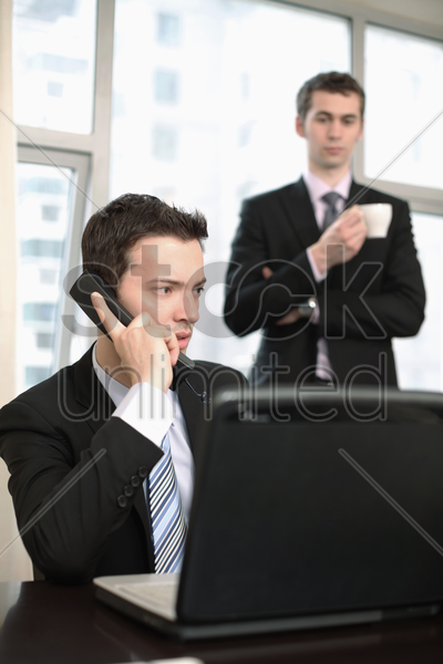 businessman talking on the phone, another businessman is watching in the background stock photo