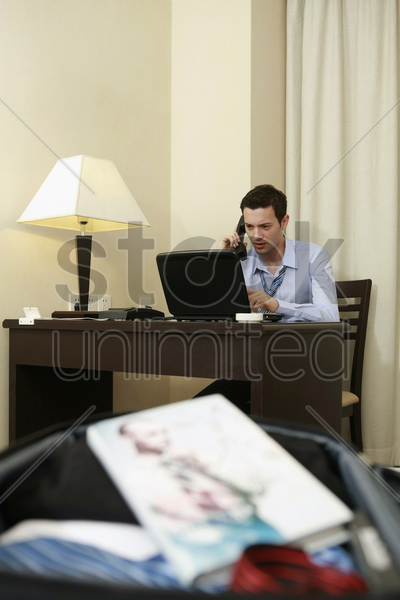 businessman talking on the phone, focus on book in the foreground stock photo