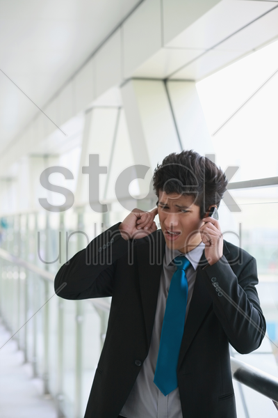 businessman talking on the phone, holding finger to ear stock photo