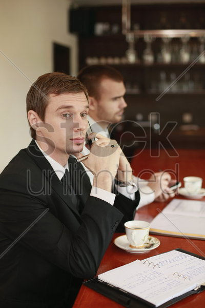 businessman talking on the phone while his colleague is text messaging on the phone stock photo