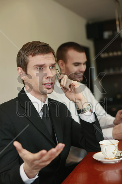 businessman talking on the phone while his colleague smiling in the background stock photo