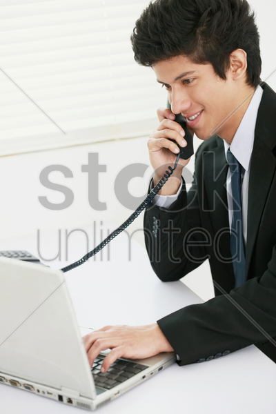 businessman talking on the phone while using laptop stock photo
