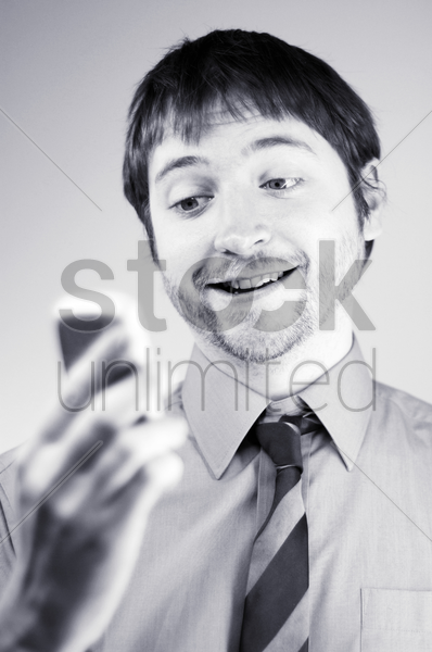 businessman text messaging on his hand phone stock photo