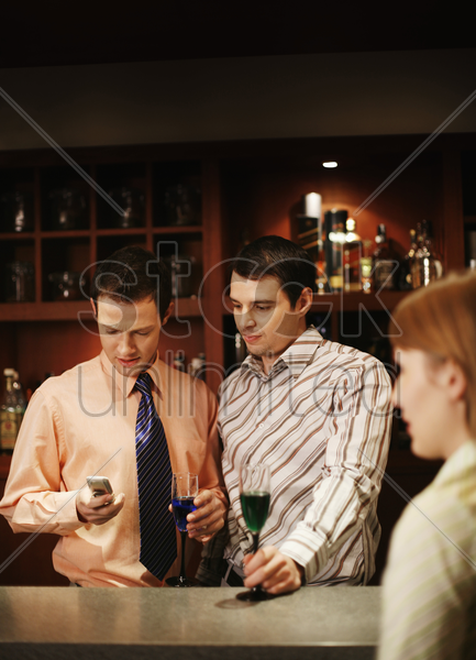 businessman text messaging on the cell phone while drinking in the bar stock photo