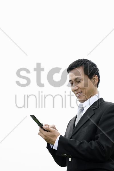 businessman text messaging on the mobile phone stock photo