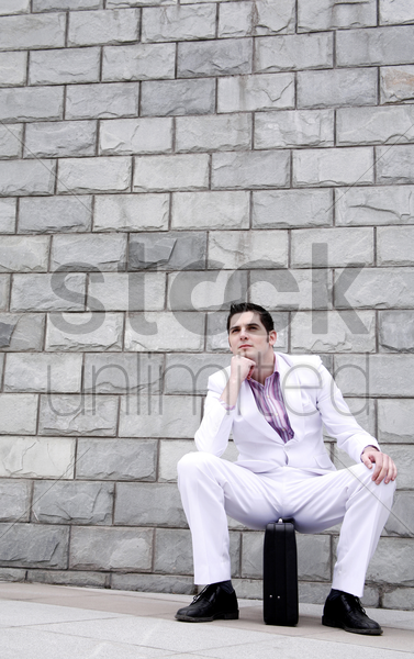 businessman thinking while sitting on briefcase stock photo