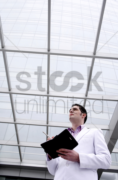 businessman thinking while writing in organizer stock photo