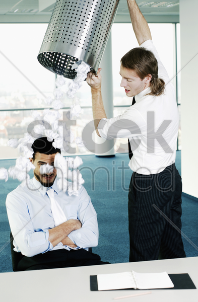 businessman throwing a dustbin of crumpled papers on his colleague stock photo