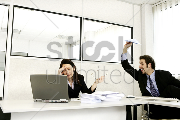businessman throwing a paper plane at his stressed up colleague stock photo