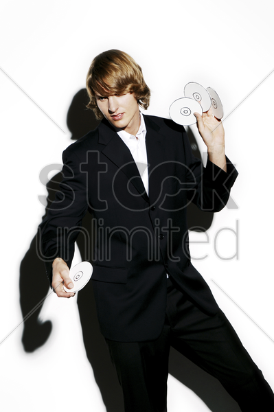 businessman throwing compact discs stock photo