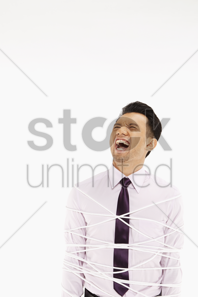 businessman tied up with a rope stock photo