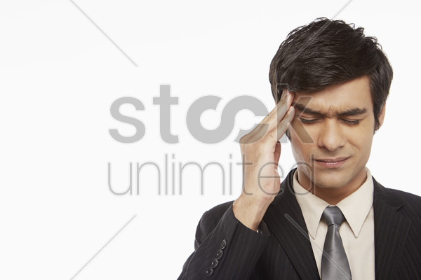 businessman touching his forehead stock photo