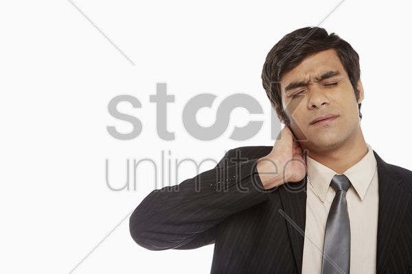 businessman touching his neck stock photo