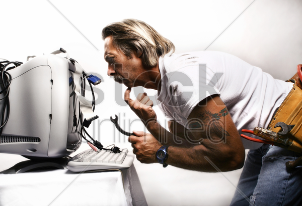 businessman trying to fix his computer stock photo