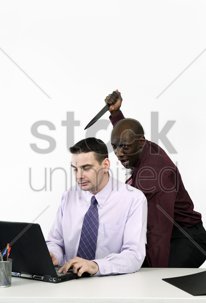 businessman trying to stab his colleague with a knife stock photo