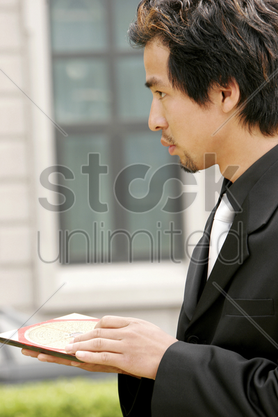 businessman using a luopan compass to check the feng shui stock photo