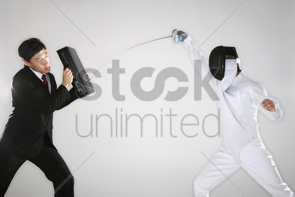 businessman using his briefcase to block another man's attack stock photo