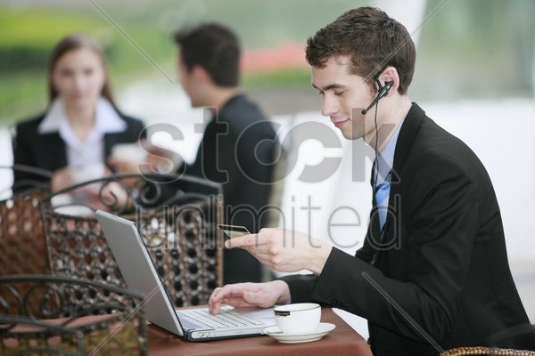 businessman using laptop and credit card to shop online at outdoor cafe stock photo