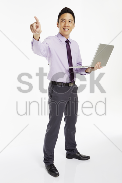businessman using laptop and pointing to the right stock photo