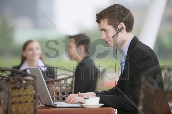 businessman using laptop at outdoor cafe stock photo