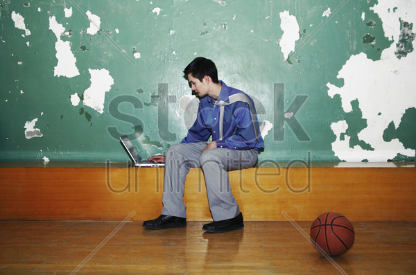 businessman using laptop in a basketball court stock photo