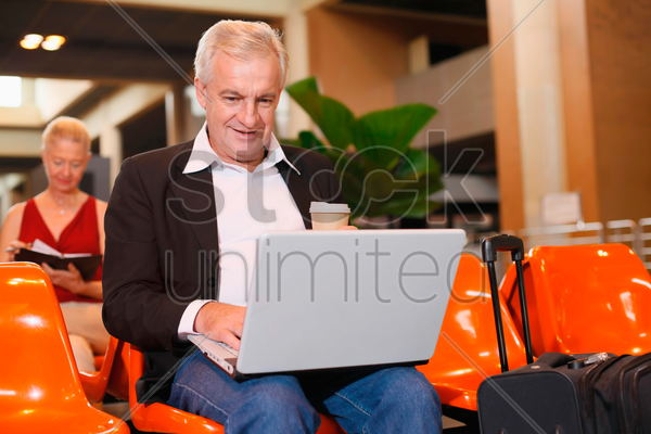 businessman using laptop in airport lounge, businesswoman with organizer in the background stock photo