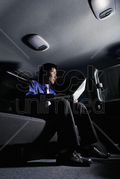 businessman using laptop in the car stock photo
