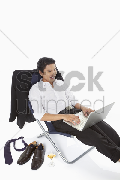 businessman using laptop while relaxing stock photo