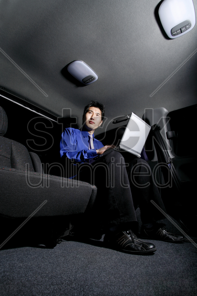 businessman using laptop while sitting in the car stock photo