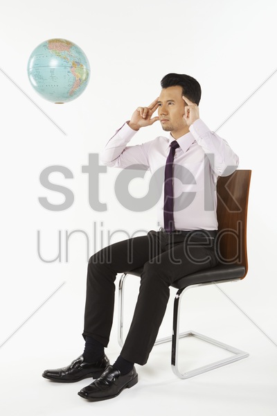 businessman using mind power to move globe stock photo
