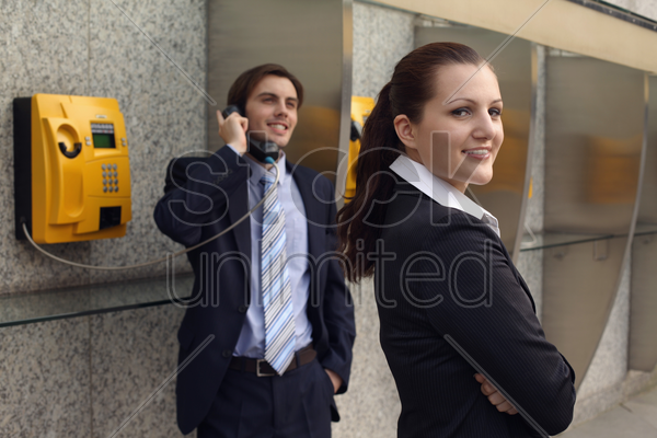 businessman using public telephone, businesswoman waiting at the side stock photo