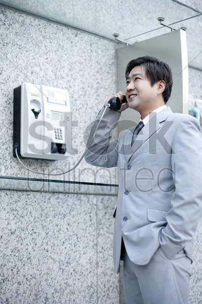 businessman using the public telephone stock photo