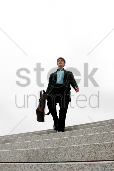 businessman walking down the stairs stock photo