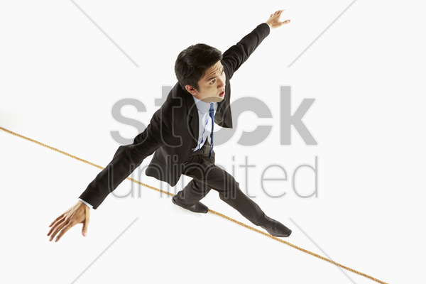 businessman walking on a rope stock photo