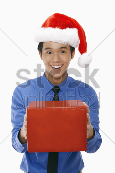 businessman wearing santa hat and holding a gift box stock photo