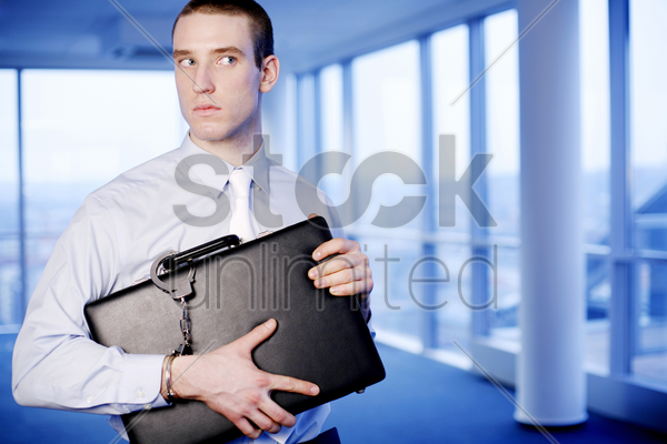businessman with a briefcase handcuffed to his wrist stock photo