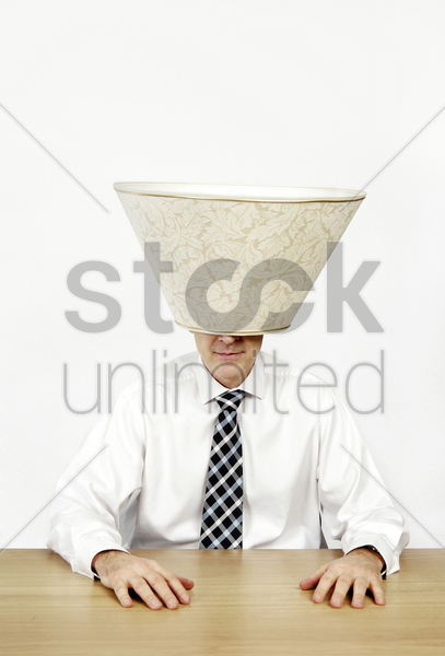 businessman with a lamp shade covering his head stock photo