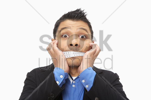 businessman with a measuring tape wrapped around his mouth stock photo