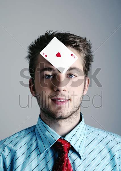 businessman with a playing card on his forehead stock photo
