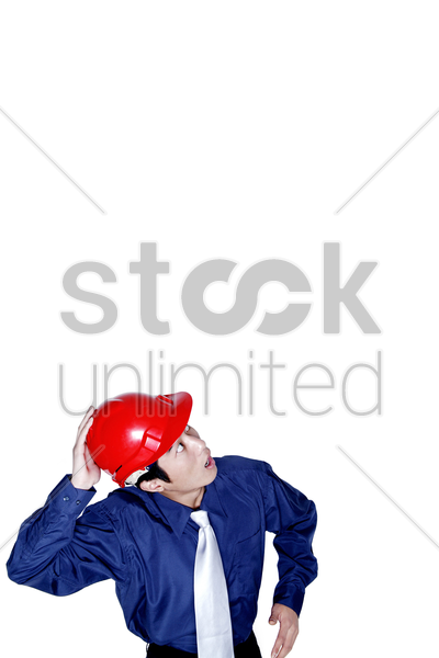 businessman with a red safety helmet looking up stock photo