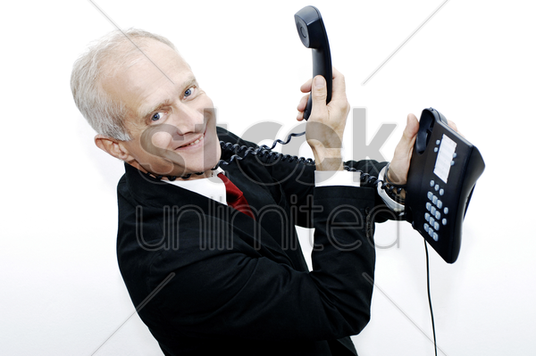 businessman with a telephone hanging around his neck stock photo