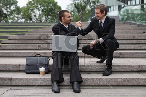 businessman with arms clasped stock photo