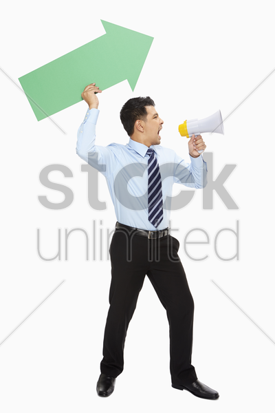 businessman with arrow shouting into a megaphone stock photo