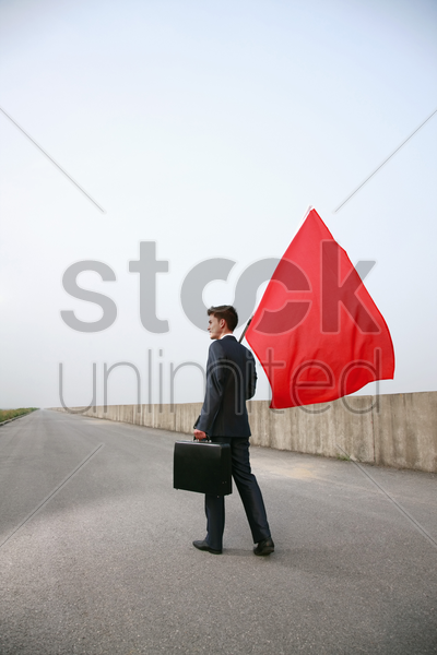 businessman with bag and red flag stock photo