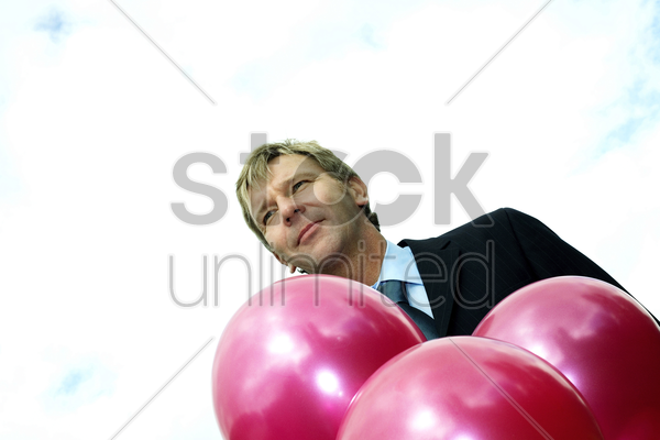 businessman with balloons stock photo